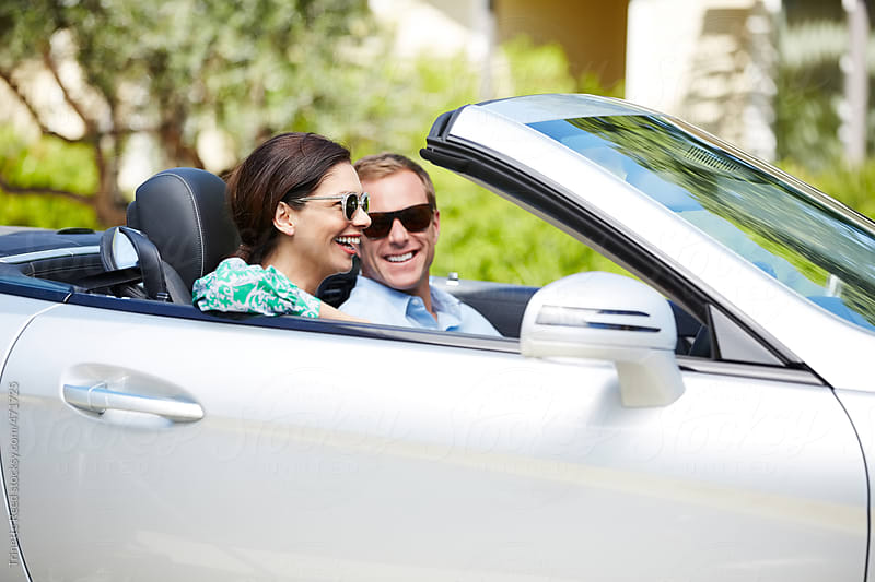 Beautiful couple going on road trip in convertible car by Trinette Reed for Stocksy United