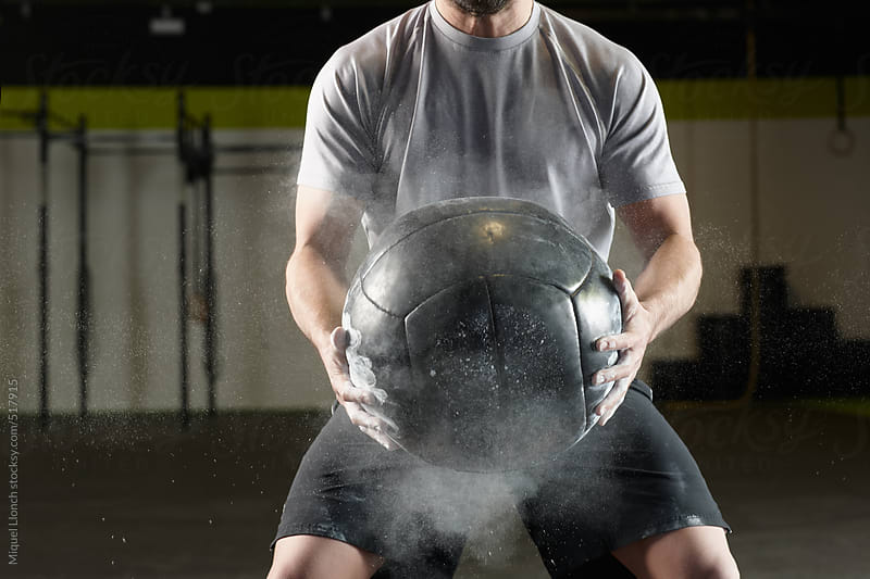 Fit man holding a weight ball in a  gym by Miquel Llonch for Stocksy United