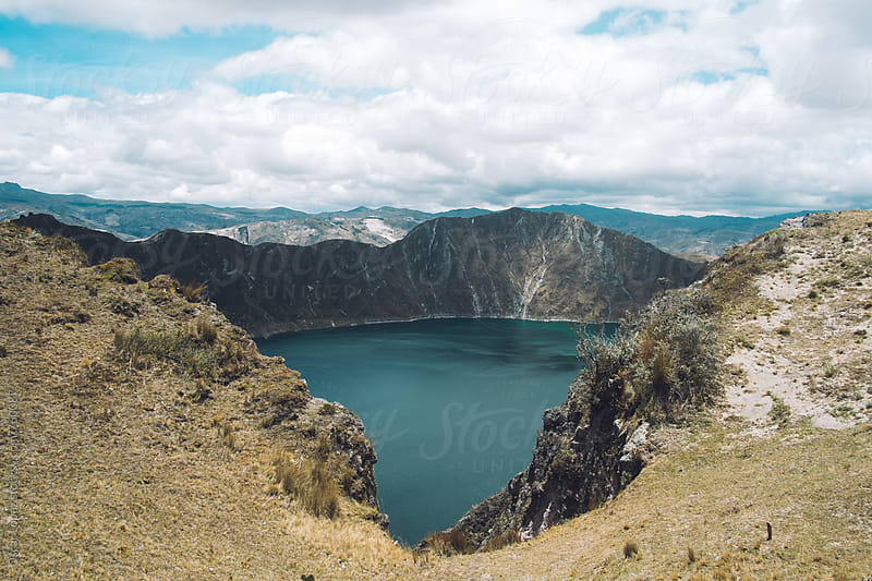 The Crater Lake Peaking through the Ridges of a Volcano by Oscar Lopez for Stocksy United