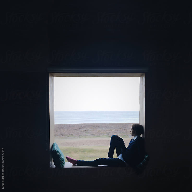 Girl looking at the sea from a window by Kirstin Mckee for Stocksy United