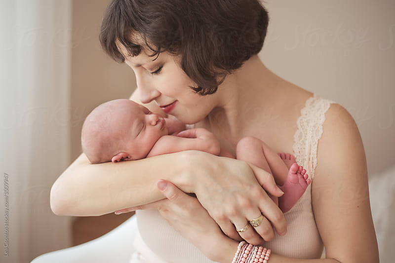 Portait of a beautiful young mother snuggling with her newborn baby by Lea Csontos for Stocksy United