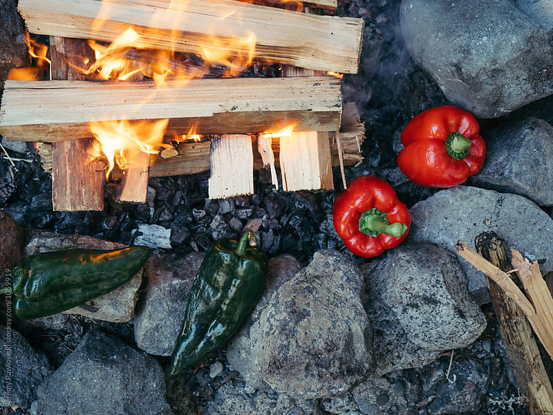 Red and green peppers roasting near campfire with open flame by Jeremy Pawlowski for Stocksy United