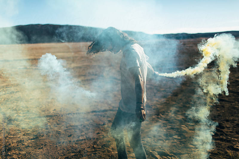a rebellious, youthful man plays with fireworks in the desert  by HOWL for Stocksy United