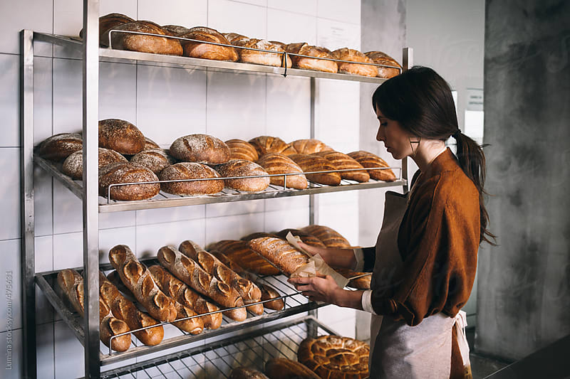 Woman Putting Bread on Shelves at a Bakery by Lumina for Stocksy United