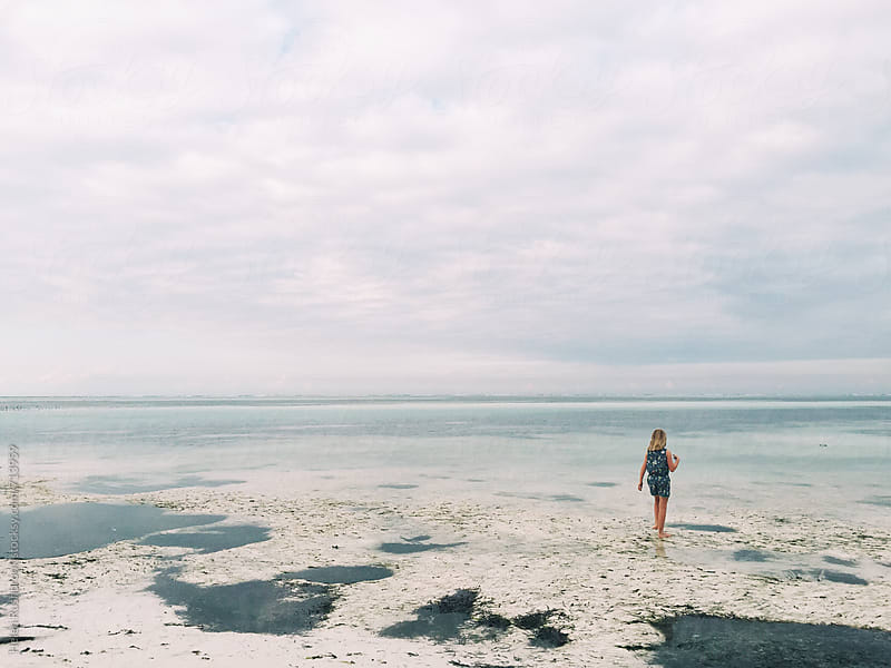 A little girl on an Indian Ocean beach at low tide in the evening. by Helen Rushbrook for Stocksy United