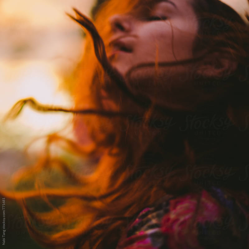Beautiful young woman in the nature day dreaming in the ray of sun by Nabi Tang for Stocksy United