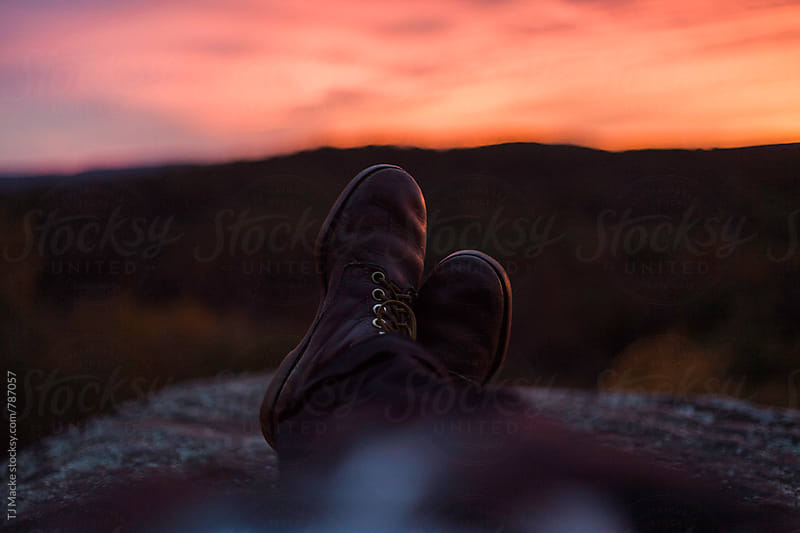 Boots crossed on the edge of a cliff at sunset by TJ Macke for Stocksy United