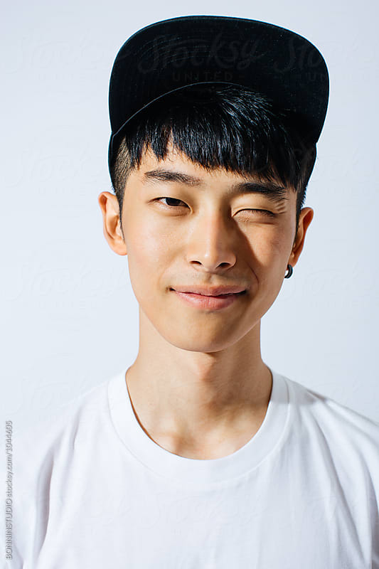 Portrait of young asian man winking in a cap over white background. by BONNINSTUDIO for Stocksy United