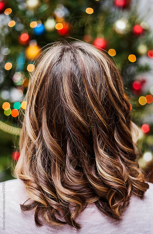 Back view of woman with curly hair, looking at christmas lights by Emoke Szabo for Stocksy United