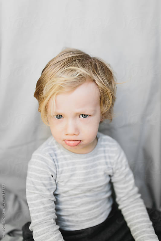 Cute Little Boy Showing Sad Facial Expression by Amir Kaljikovic for Stocksy United