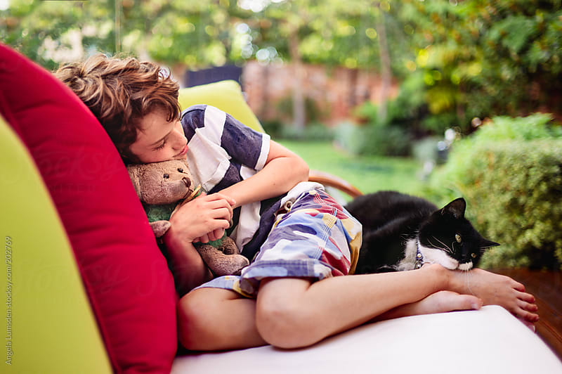 Child resting with cat and teddy bear in garden by Angela Lumsden for Stocksy United