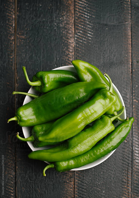 Green peppers on a wooden table by Davide Illini for Stocksy United