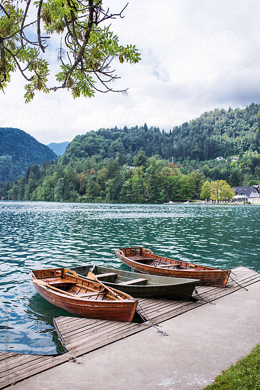 Lonely boats floating on lake Bled by Lea Csontos for Stocksy United