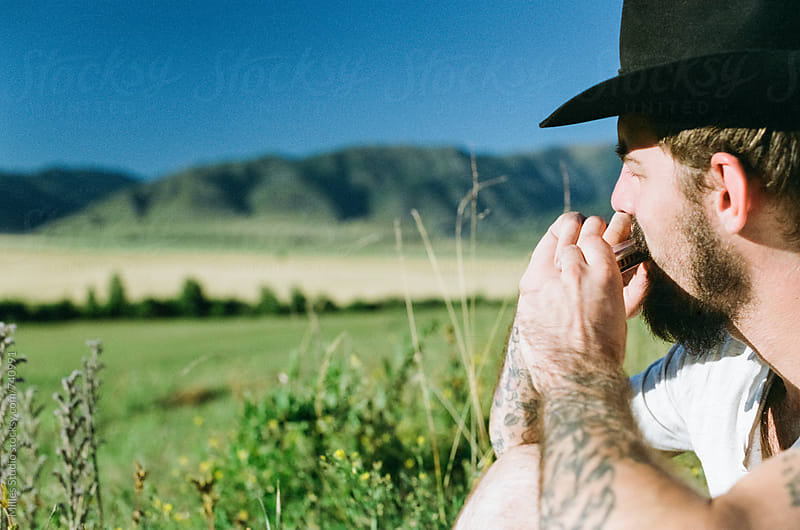 Man playing on harmonica  by Milles Studio for Stocksy United