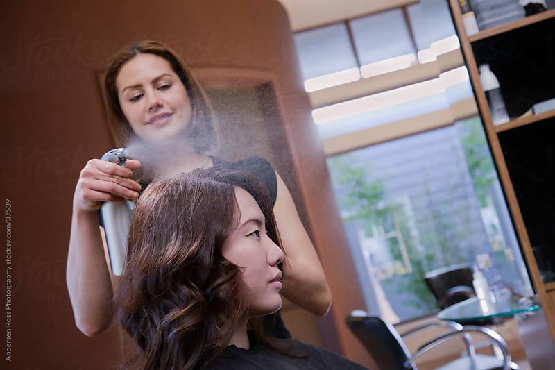 Hairdresser spraying  customer's hair by Andersen Ross Photography for Stocksy United