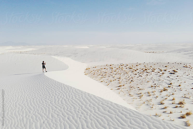 Man Taking Pictures From White Sand Dune by Kevin Russ for Stocksy United