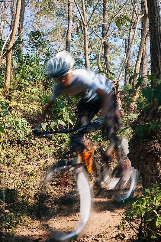 A mountain biker racing down a hill. Blurred motion. by Shikhar Bhattarai for Stocksy United