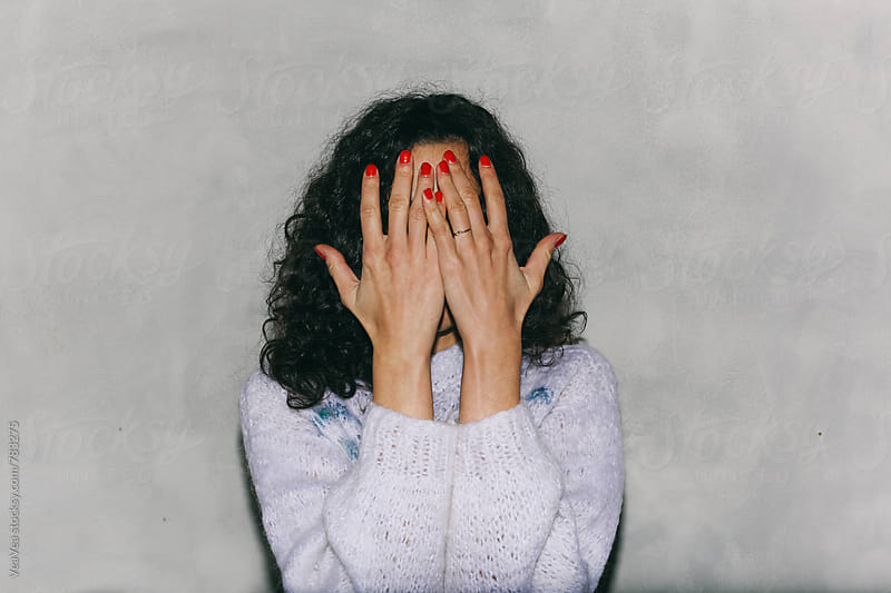 Woman covering her face with her hands. In front of a white wall, flash light. by Marija Mandic for Stocksy United