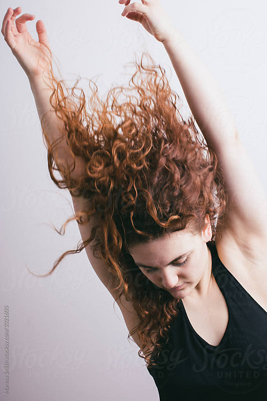 A redhead dancer moving and stretching, her hair is  caught up in the movement by Maresa Smith for Stocksy United