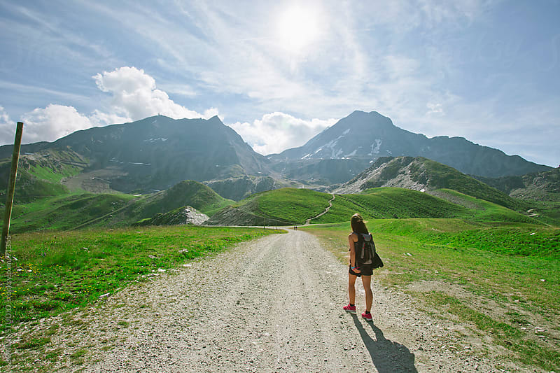 Back view of hiker woman walking on  beautiful natural road. Alps, france. by BONNINSTUDIO for Stocksy United