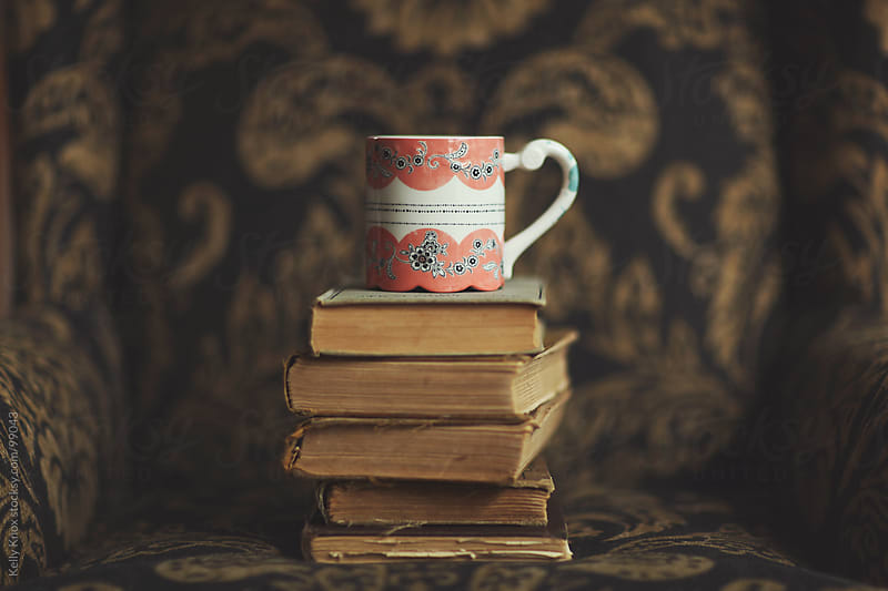 a coffee mug stacked on top of old books by Kelly Knox for Stocksy United