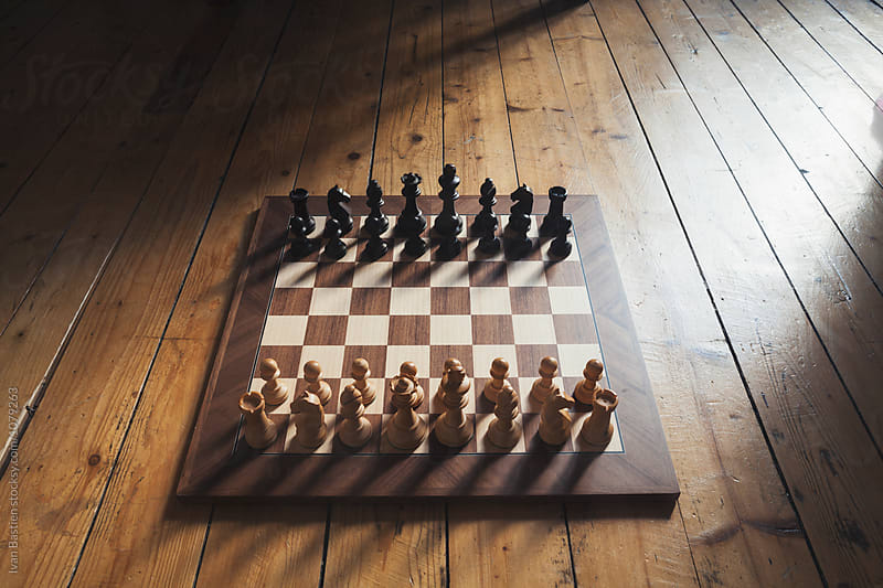 Wooden chess board on parquet by Ivan Bastien for Stocksy United