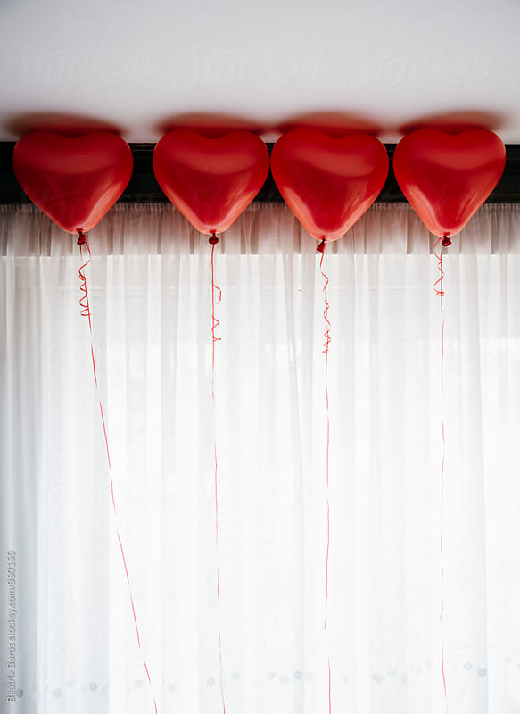 4 heart balloons in front of a white curtain by Beatrix Boros for Stocksy United