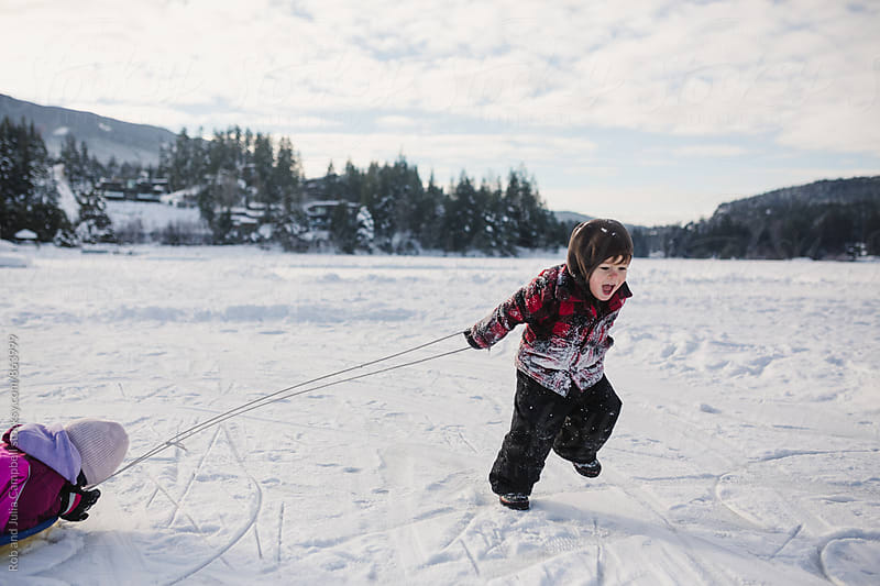 Happy little boy pulling kid on sled in winter by Rob and Julia Campbell for Stocksy United