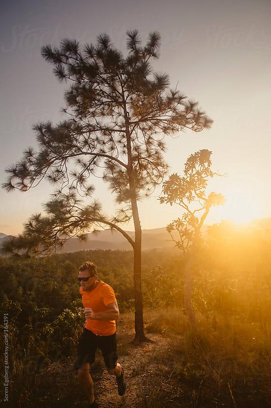 Runner backlit by sunset by Soren Egeberg for Stocksy United