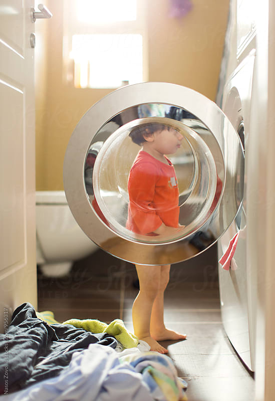 1 year old boy looking a washing machine by Nasos Zovoilis for Stocksy United