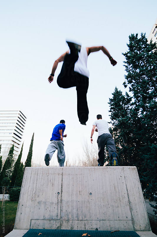 Low angle view of man jumping after his friends during parkour session on the city by Inuk Studio for Stocksy United
