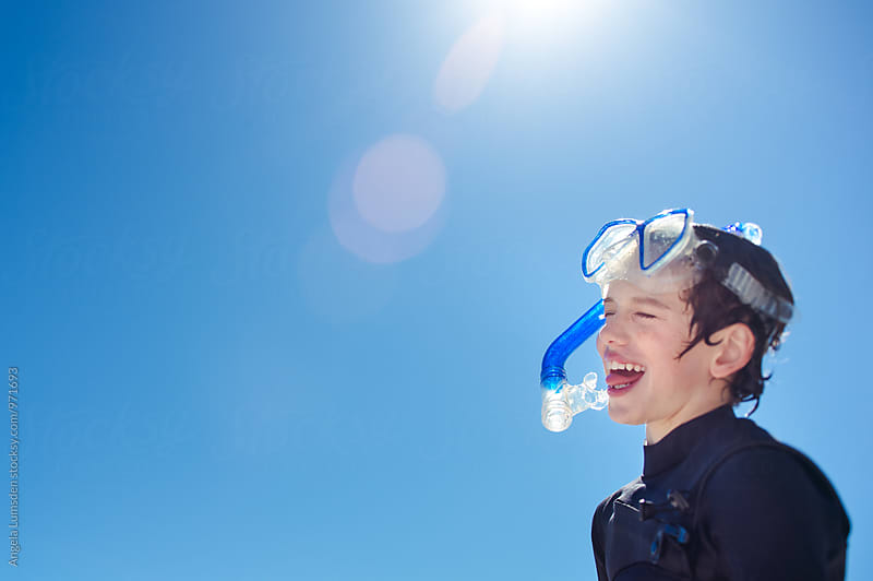 Happy child wearing a snorkel set and wetsuit smiles in the sun by Angela Lumsden for Stocksy United