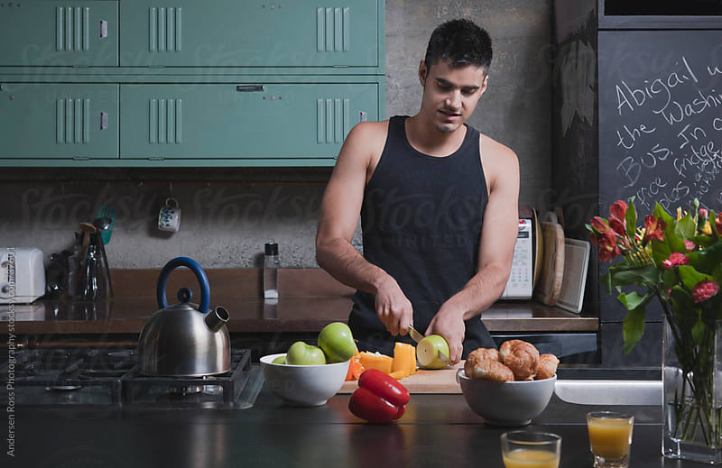 Man cooking in kitchen by Andersen Ross Photography for Stocksy United
