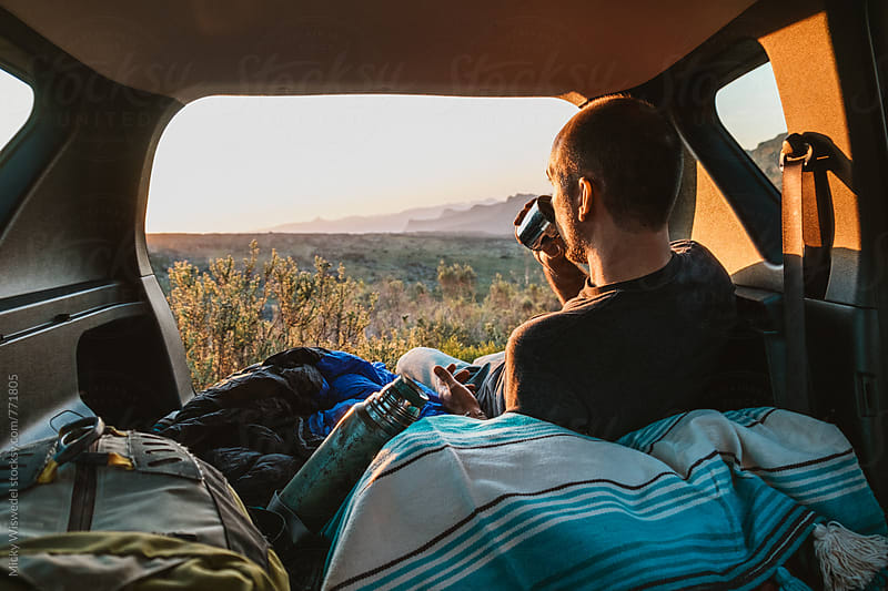 Man camped in the back of his car having a drink and watching the sunset outdoors by Micky Wiswedel for Stocksy United