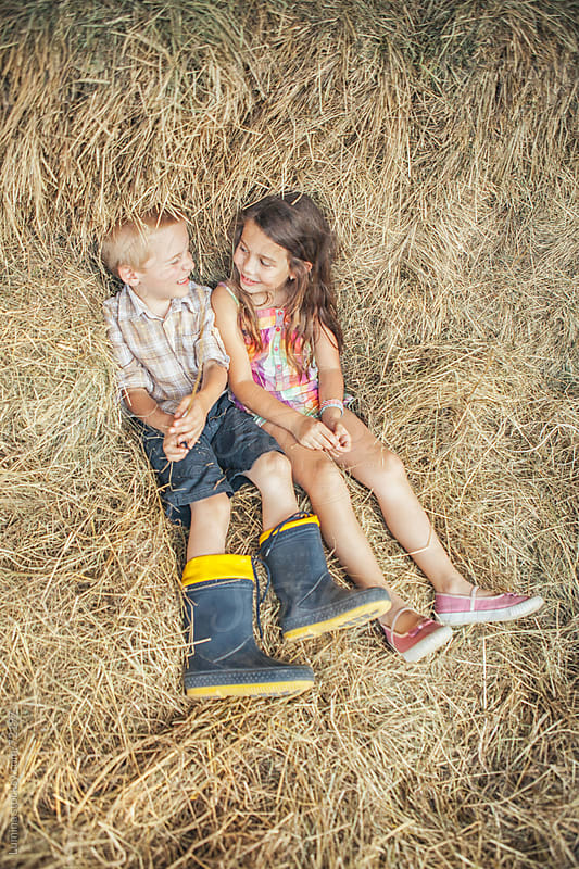 Boy and Girl Sitting in Straw by Lumina for Stocksy United