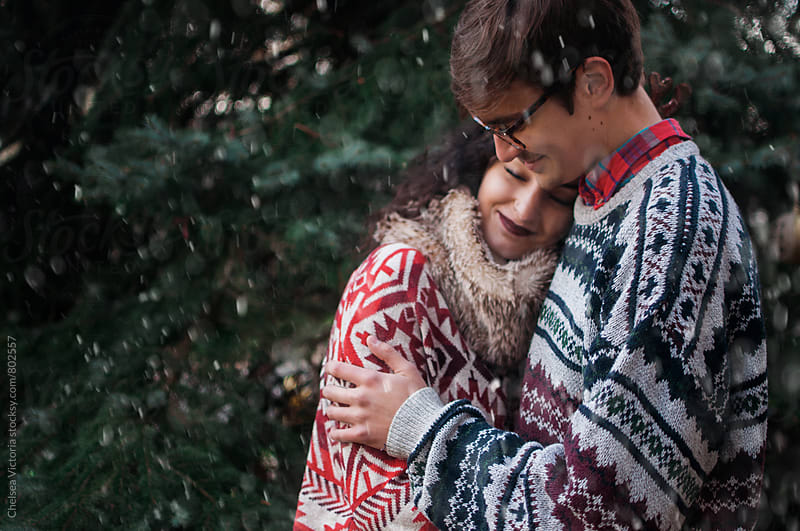 A young couple dressed in holiday sweaters by Chelsea Victoria for Stocksy United