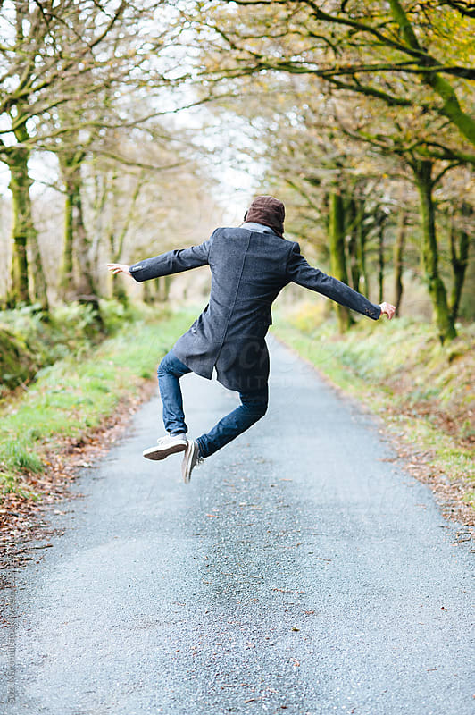 Man jumping in the air and clicking his heels by Suzi Marshall for Stocksy United