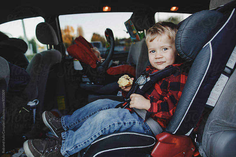 Cute toddler boy in carseat smiling and eating muffin by Rob and Julia Campbell for Stocksy United