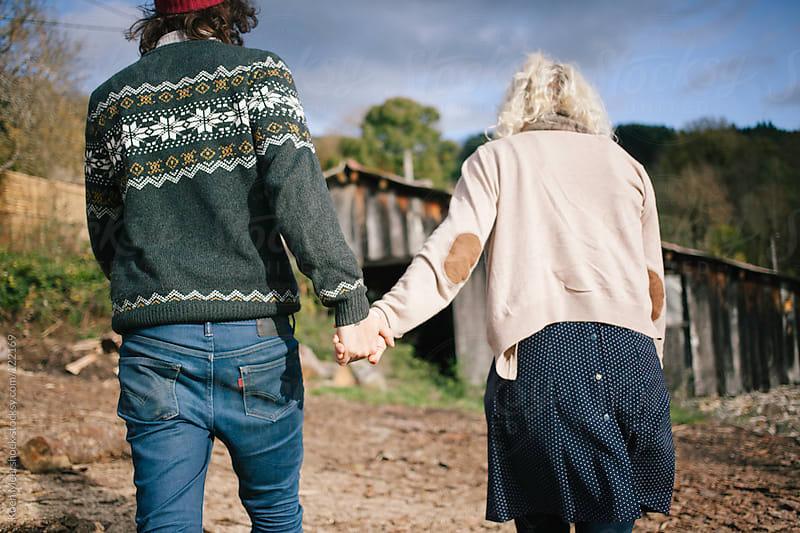Couple in love walking hand in hand towards a barn. by Koen Meershoek for Stocksy United