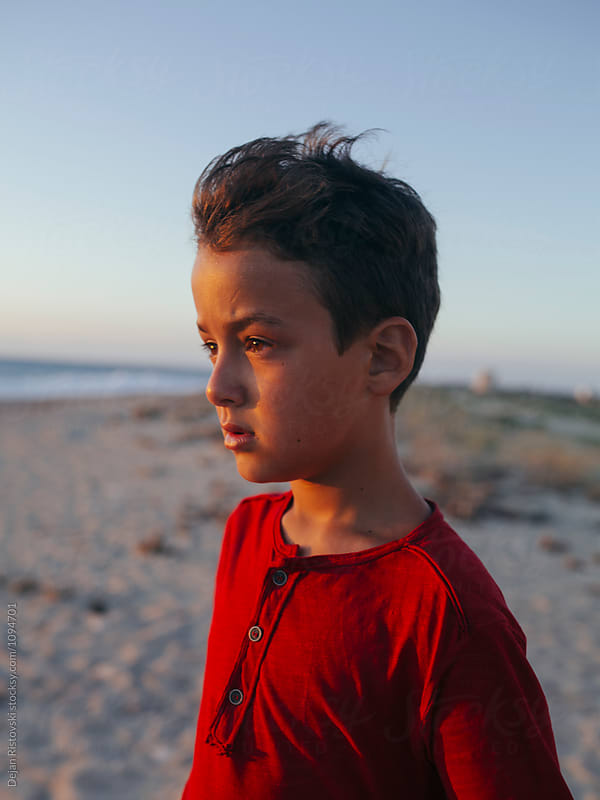 Boy looking at the sunset. by Dejan Ristovski for Stocksy United
