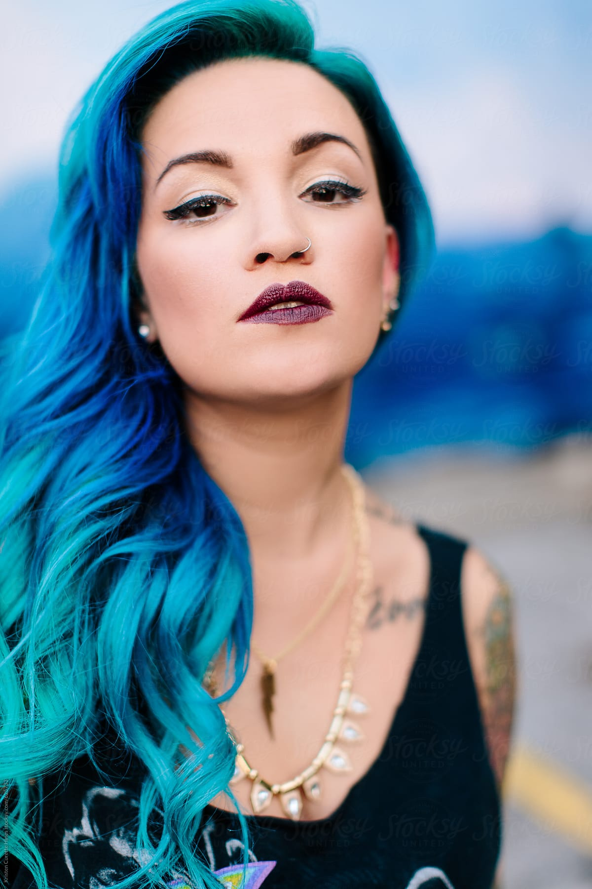 Vertical Portrait Of A Beautiful Hispanic Woman With Blue Dyed Hair By Kristen Curette Daemaine Hines Stocksy United