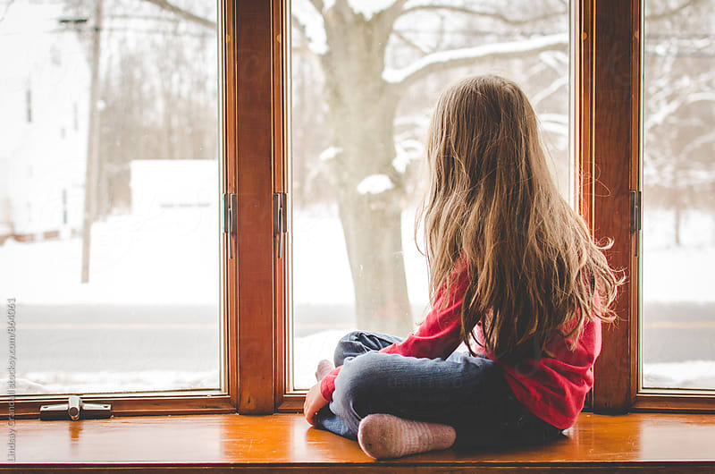 Girl sitting beside a snowy window by Lindsay Crandall for Stocksy United
