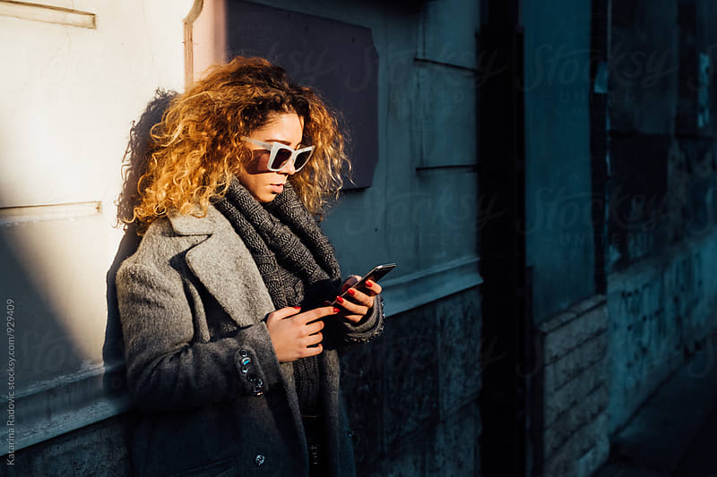 Young Woman With Curly Hair And Sunglasses Using her Phone by Katarina Radovic for Stocksy United