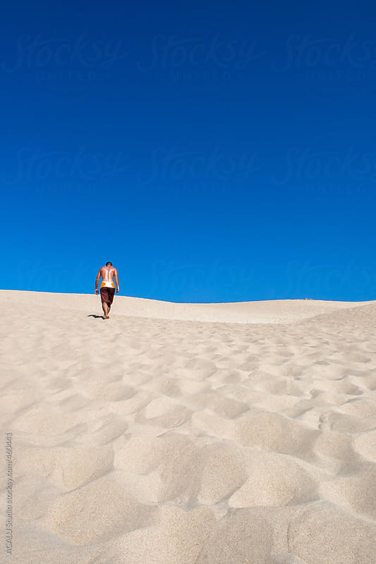 Man walking by dune in Cadiz beach by ACALU Studio for Stocksy United