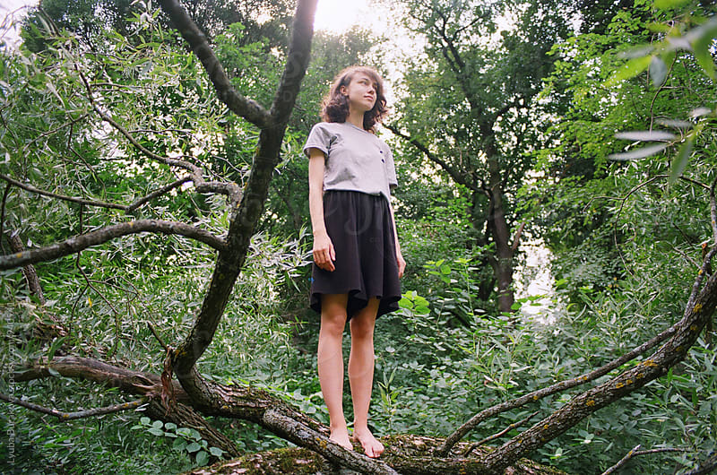 Young woman standing on a fallen tree by Liubov Burakova for Stocksy United