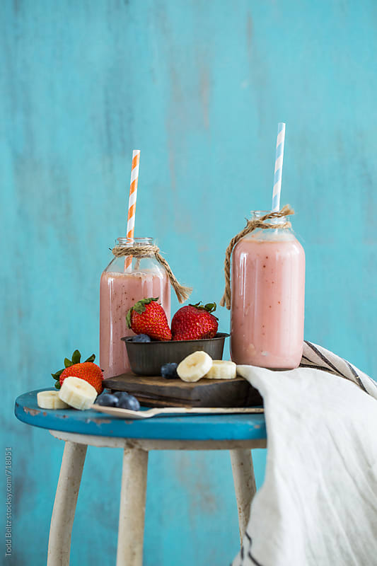 Homemade fruit smoothies against a blue background by Todd Beltz for Stocksy United