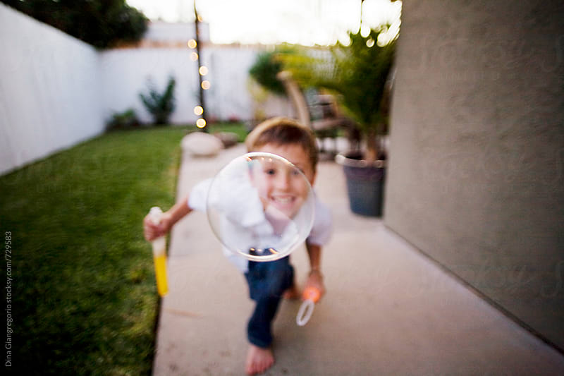 Boy Outdoors Looking Through a Bubble by Dina Giangregorio for Stocksy United