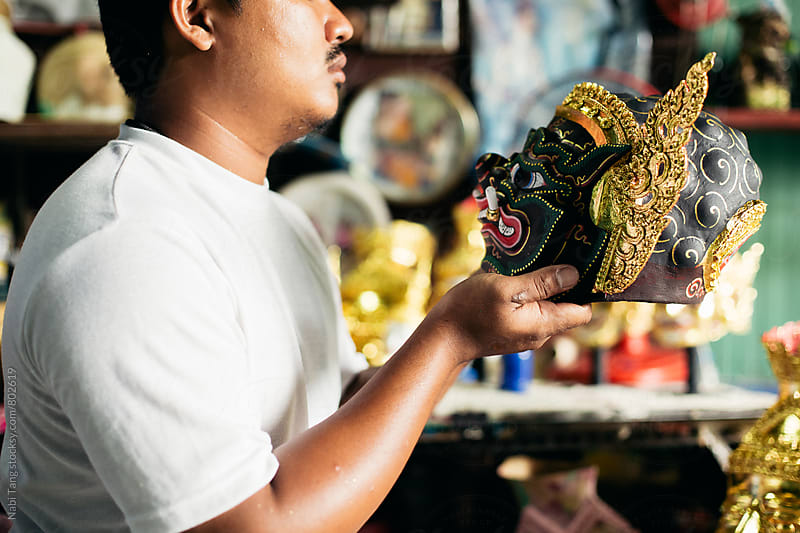Artist holding 'Hua Khon' traditional mask for Thai performing arts by Nabi Tang for Stocksy United