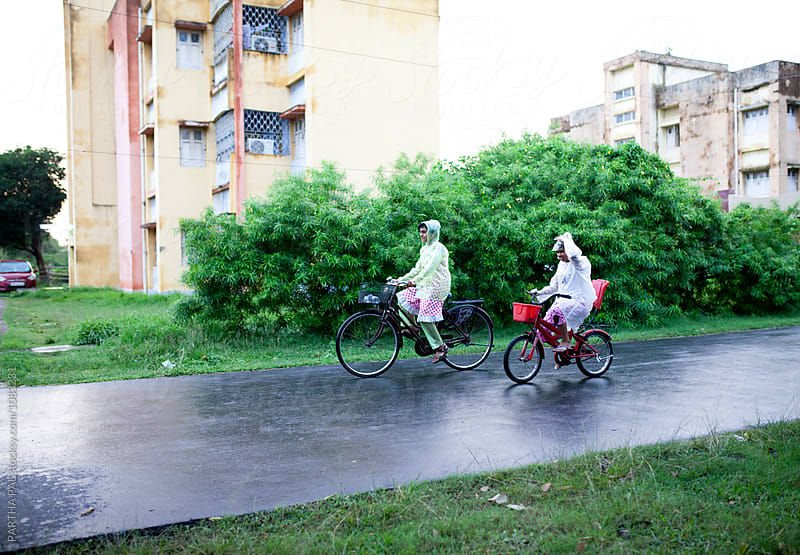 Teenagers wearing rain proof and cycling by PARTHA PAL for Stocksy United