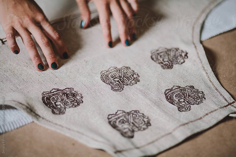 Crop woman stamping on fabric  by Sergey Filimonov for Stocksy United